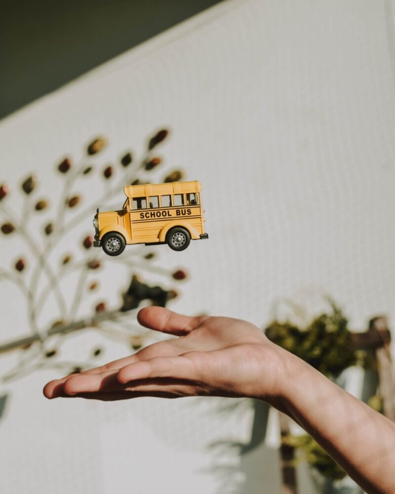 mini school bus toy thrown up from the hand